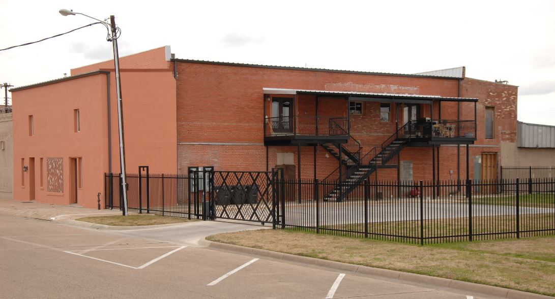 Exterior of brick building with fence and staircases