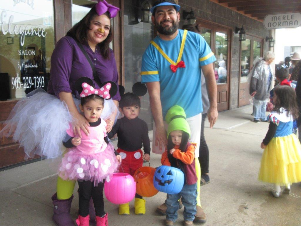 Family trick-or-treating in costumes