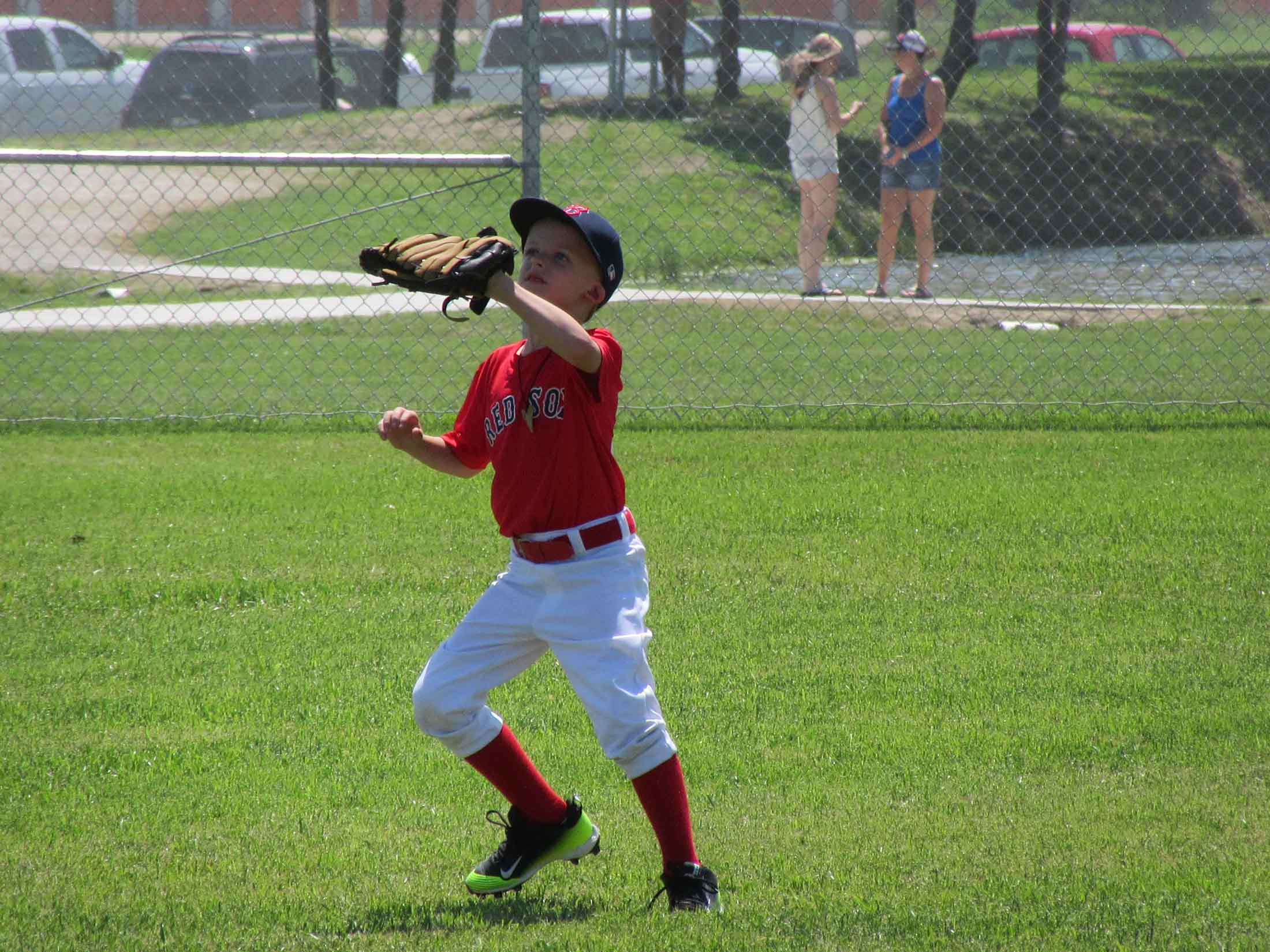 Boy in red shirt catching a ball