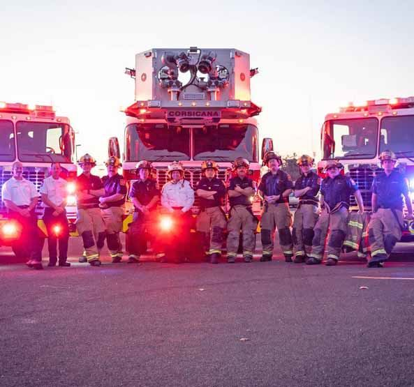 Corsicana Fire Fighters Standing in Front of Three Fire Trucks